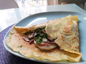 crepes au lardons, champignon et fromage de chevre pliée dans une assiette