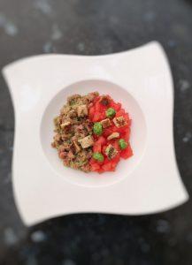 tartare de veau et de tomate avec du pesto maison dans une assiette creuse